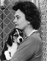 Ann Cottrell Free holding a laboratory beagle.