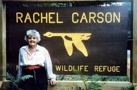 Ann Cottrell Free in front of Rachel Carson Wildlife Refuge sign.